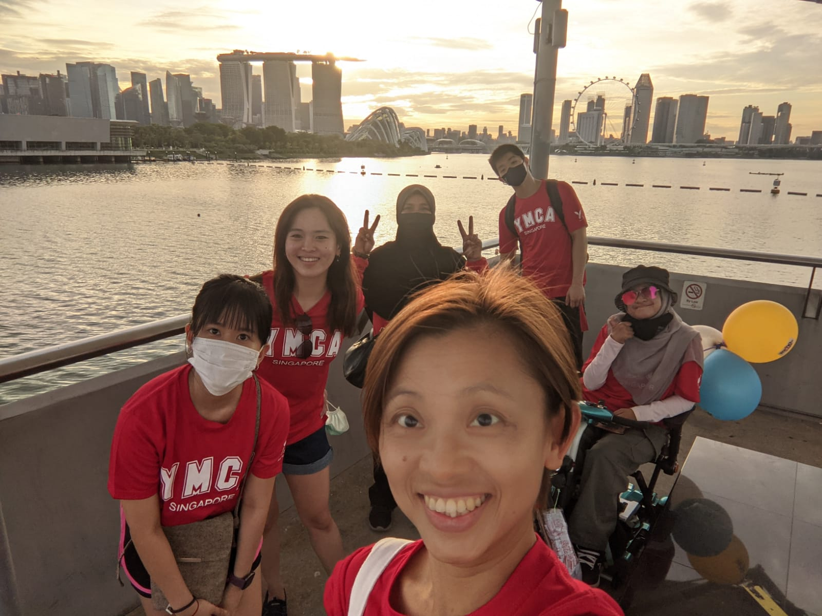 A team consisting of Hwee Hoon, Ana, Mei Wah, Chuan Zheng, Sabrina & her mum smiling into the camera with a beautiful sunset in the background.